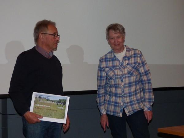 Pristagaren Uno Holmberg med priset som han just mottagit av föreningens ordförande Evastina Blomgren
